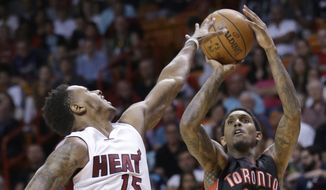 Toronto Raptors guard Louis Williams (23) goes up for a three-point shot against Miami Heat guard Mario Chalmers (15) during the second half of an NBA basketball game, Saturday, April 11, 2015, in Miami. Williams finished the night with 29 points as the Raptors defeated the Heat 107-104. (AP Photo/Wilfredo Lee)