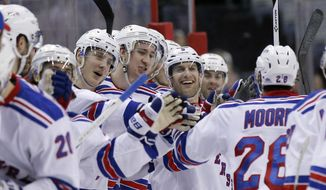 New York Rangers center Dominic Moore (28) celebrates his goal with his teammates in the second period of an NHL hockey game against the Washington Capitals, Saturday, April 11, 2015, in Washington. (AP Photo/Alex Brandon)