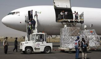 Aid workers unload humanitarian relief supplies for civilians affected by a Saudi-led airstrike campaign from a cargo plane at the airport in Sanaa, Yemen, Saturday, April 11, 2015. (AP Photo/Hani Mohammed)