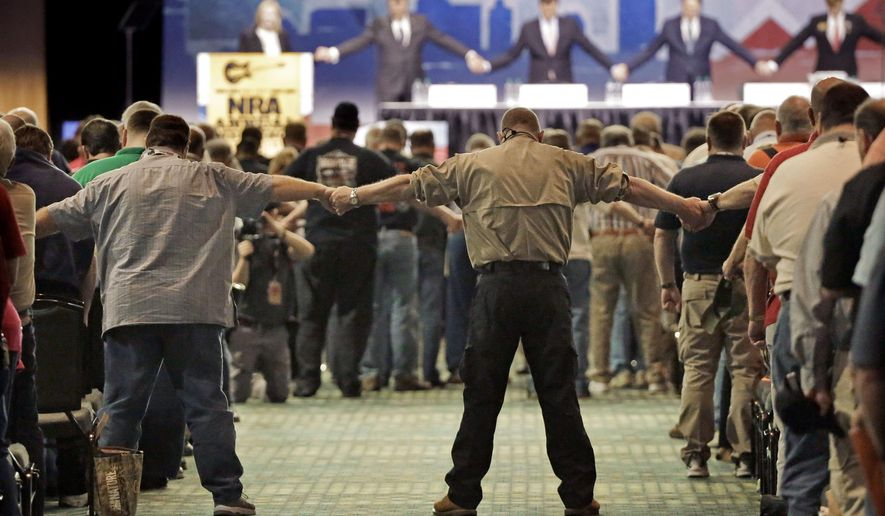 National Rifle Association members hold hands during the opening prayer at the annual meeting of members at the NRA convention Saturday, April 11, 2015, in Nashville, Tenn. (AP Photo/Mark Humphrey)