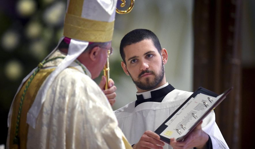 MEMBER FEATURE EXCHANGE FOR APRIL 11 -- In this April 1, 2015 photo, seminarian Michael Bovino, right, of Stonington, Conn., assists Most Rev. Michael R. Cote, Bishop of Norwich, in the Chrism Mass at the Cathedral of St. Patrick in Norwich, Conn. Bovino is in his first year at Mount St. Mary's Seminary in Maryland. (AP Photo/The Day, Tim Cook) MANDATORY CREDIT