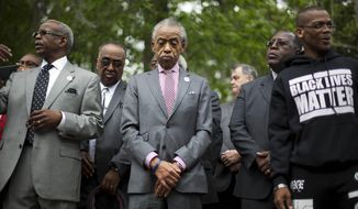 The Rev. Al Sharpton, center, visits a makeshift memorial where Walter Scott was fatally shot by a white police officer after he fled a traffic stop, Sunday, April 12, 2015, in North Charleston, S.C. The officer, Michael Thomas Slager, has been fired and charged with murder. (AP Photo/David Goldman)