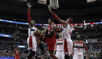 Atlanta Hawks guard Kent Bazemore (24) looks to pass between Washington Wizards guard John Wall, left, and Washington Wizards forward Paul Pierce (34) in the first half of an NBA basketball game Sunday, April 12, 2015, in Washington. (AP Photo/Alex Brandon)