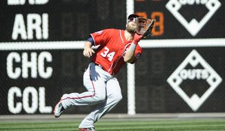 Washington Nationals right fielder Bryce Harper catches a fly ball, hit by Philadelphia Phillies' Jeff Francoeur, in the fourth inning of a baseball game Sunday, April 12, 2015, in Philadelphia. (AP Photo/Michael Perez)