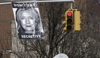 An unknown artist placed a poster on a traffic signal in front of the building where Hillary Rodham Clinton's presidential campaign offices are located, Sunday, April 12, 2015 in the Brooklyn borough of New York. A top adviser to Clinton announced her much-awaited second campaign for the White House on Sunday in an email to alumni of her first presidential campaign. (AP Photo/Mark Lennihan)