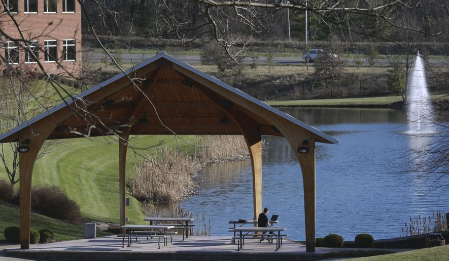 A man sits at a table by an outdoor pavilion next to a pond and fountain at the Virginia Tech Corporate Research Center in Blacksburg, Va.,  Wednesday April 1 2015.  Since 2001, the research and office park has maintained a paid gym on its campus to give both the general public and employees of the many small companies there a recreational outlet during the lunch or after-work hours.(AP Photo / The Roanoke Times, Matt Gentry)