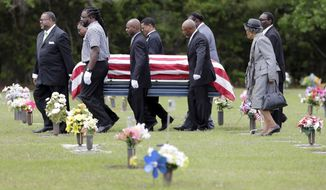 Pallbearers walk Walter Scott's casket to the gravesite for his burial service in Charleston, S.C. on Saturday, April 11, 2015. Scott was fatally shot by a North Charleston, S.C., police officer a week earlier after a traffic stop. Officer Michael Slager has been charged with murder.