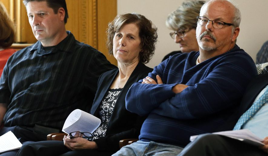 Jane Dougherty, center, whose sister was killed in the Newtown, Conn., school shooting in 2012, sits with Dave Hoover, left, and Tom Sullivan, both of whom lost close family members in the Aurora, Colo., movie theater shooting, listening to testimony on bills aimed at undoing recent firearm laws, at the state Legislature, in Denver, Monday April 13, 2015. Lawmakers considered several proposals, including two Republican-sponsored bills to eliminate gun-control measures passed by Democrats in 2013. (AP Photo/Brennan Linsley)