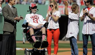 Pete Frates, a former Boston College baseball player stricken with ALS whose Ice Bucket Challenge has raised millions for ALS research, is applauded by Boston Red Sox general manager Ben Cherington, far left, and his wife Julie Frates, middle, along with other family members prior to the home opener baseball game between the Boston Red Sox and the Washington Nationals at Fenway Park in Boston, Monday, April 13, 2015. (AP Photo/Elise Amendola)