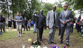 The Rev. Al Sharpton, right, visits a makeshift memorial where Walter Scott was fatally shot by a white police officer after he fled a traffic stop, Sunday, April 12, 2015, in North Charleston, S.C. The officer, Michael Thomas Slager, has been fired and charged with murder. (AP Photo/David Goldman)
