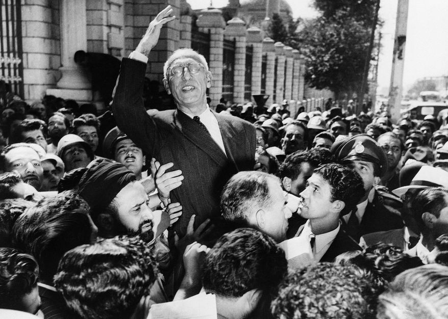 Iranian Premier Mohammed Mossadegh rides on the shoulders of cheering crowds in Tehran's Majlis Square, Sept. 27, 1951, outside the parliament building, after reiterating his oil nationalization views to his public supporters. The frail premier, whose demands for the ouster of British oil interests have created international tension, is awaiting Oct. 1, a possible summons to appears before the United Nations Security Council in New York.(AP Photo)