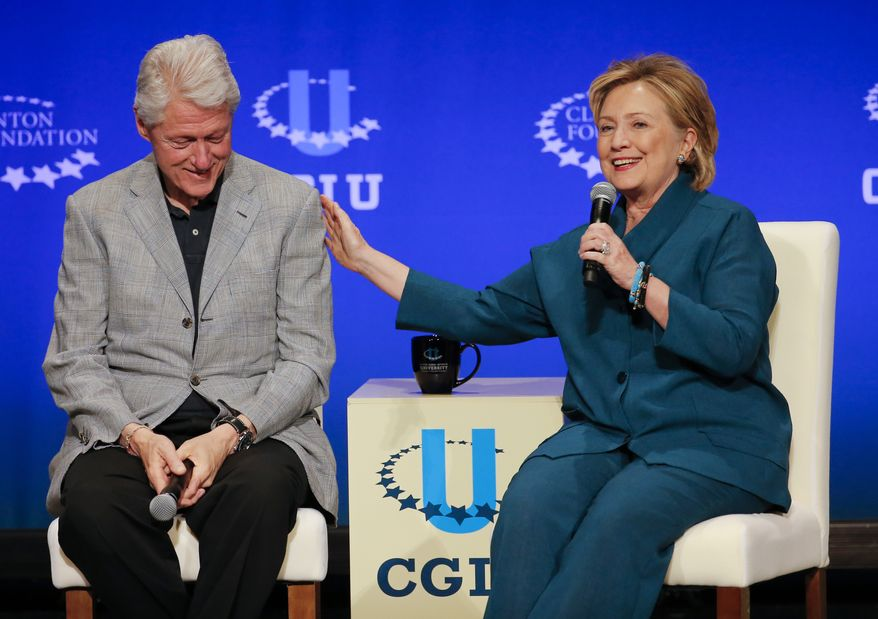 Former President Bill Clinton, left, listens as former Secretary of State Hillary Rodham Clinton speaks during a student conference for the Clinton Global Initiative University at Arizona State University. (AP Photo/Matt York, File)