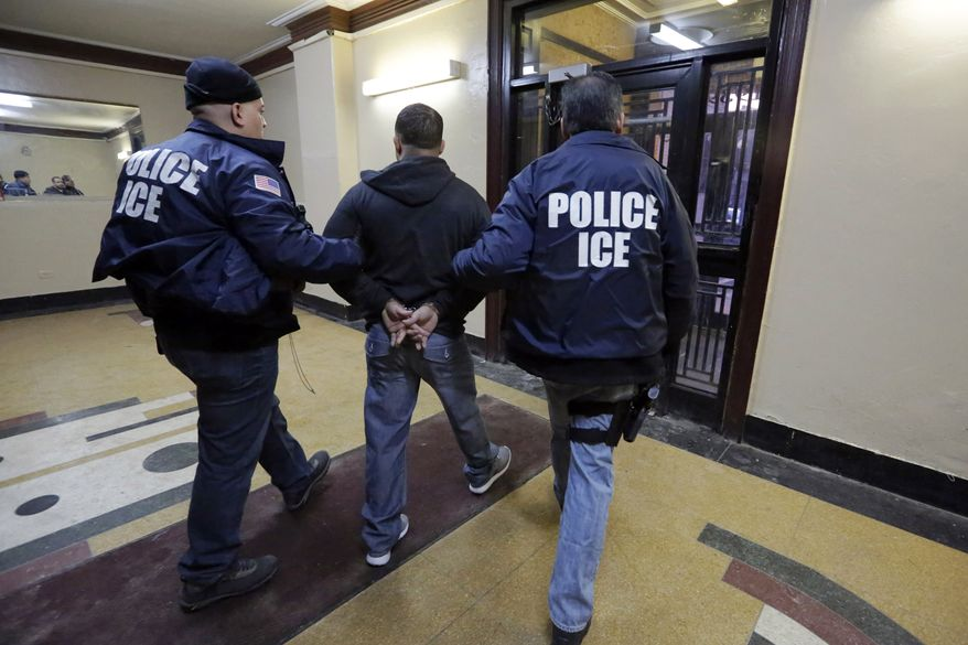 Immigration and Customs Enforcement officers escort an arrestee from an apartment building in the Bronx borough of New York during a series of early-morning raids on March 3. (Associated Press)