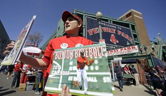 Kim Sudenfield sells programs outside Fenway Park prior to the home opener  baseball game between the Boston Red Sox and the Washington Nationals in Boston, Monday, April 13, 2015. (AP Photo/Elise Amendola)