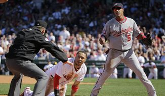 Washington Nationals third baseman Yunel Escobar (5) reacts as Boston Red Sox's Mookie Betts is called safe after stealing third base in the first inning of the home opener baseball game at Fenway Park in Boston, Monday, April 13, 2015. (AP Photo/Elise Amendola)