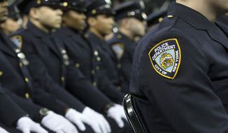 In this Dec. 29, 2014, file photo, new recruits attend their New York Police Academy graduation ceremony at Madison Square Garden in New York. (AP Photo/John Minchillo, File)