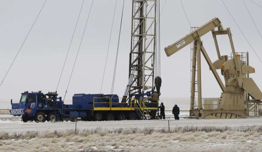FILE - In this Dec. 15, 2014 file photo, workers drill for oil at a site near Williston, N.D. North Dakota lawmakers are looking at a project to treat and recycle oil drilling waste for road building and other uses. The measure would set aside about $65,000 for the state Health Department to monitor a project and develop standards. (AP Photo/Eric Gay, File)