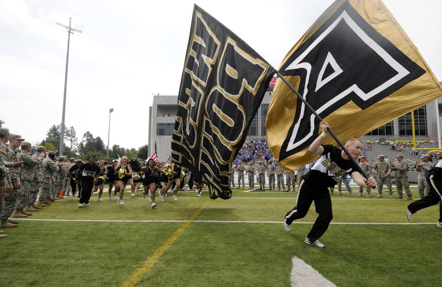 FILE - In this Sept. 6, 2014, file photo, Army cheerleaders and players take the field before an NCAA college football game against Buffalo in West Point, N.Y. Army is getting a new look. The academy unveiled a rebranding Monday night, April 13, 2015, after an 18-month collaboration with Nike.  One goal is to strengthen the connection between Army and West Point. The academy will now refer to its teams as Army West Point instead of just Army. (AP Photo/Hans Pennink, File)