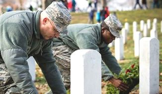 Air Force personnel place wreaths at graves in Arlington National Cemetery, in Arlington, Va., Dec. 13, 2014. (Image: U.S. Air Force) ** FILE **