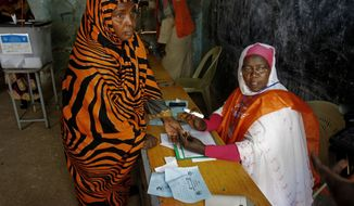 A Sudanese woman prepares to vote on the second day of Sudan's presidential and legislative elections, in Izba, an impoverished neighborhood on the outskirts of Khartoum, Sudan, Tuesday, April 14, 2015. (AP Photo/Abd Raouf)