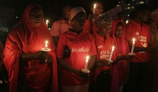 People hold candles during a vigil to mark the one year anniversary of the abduction of girls studying at the Chibok government secondary school, Abuja, Nigeria, Tuesday, April 14, 2015. On the first anniversary of the day 276 schoolgirls were snatched in the middle of the night as they prepared to write science exams at their boarding school in northeastern Nigeria, President-elect Muhammadu Buhari said he cannot promise to find the 219 who are still missing. (AP Photo/Sunday Alamba)
