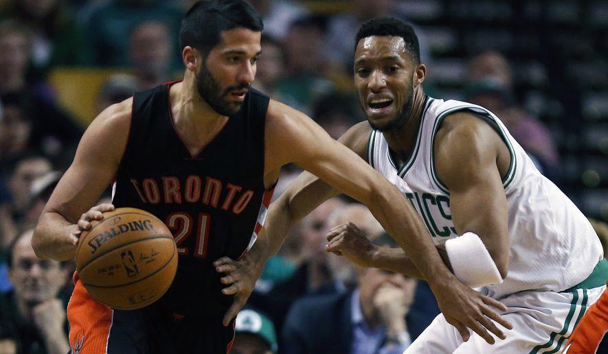 Toronto Raptors' Greivis Vasquez (21) drives past Boston Celtics' Evan Turner during the first quarter of an NBA basketball game in Boston, Tuesday, April 14, 2015. (AP Photo/Michael Dwyer)