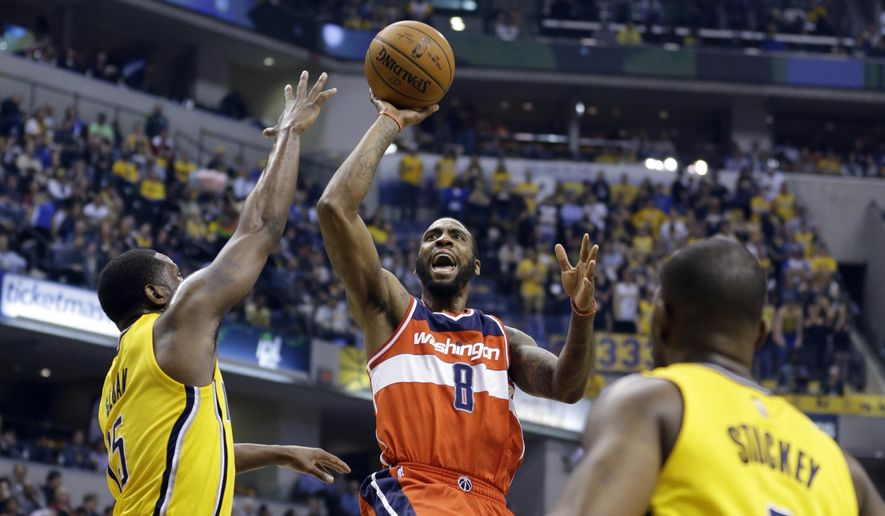 Washington Wizards forward Rasual Butler (8) shoots between Indiana Pacers guard Donald Sloan (15) and guard Rodney Stuckey (2) during the first half of an NBA basketball game in Indianapolis, Tuesday, April 14, 2015. (AP Photo/Michael Conroy) **FILE**