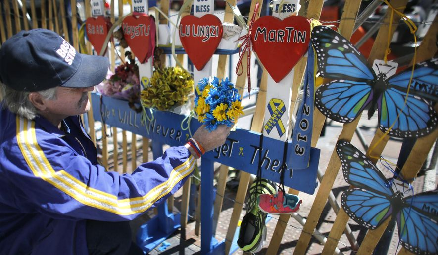 Kevin Brown, of Brockton, Mass., attaches flowers to a memorial near one of two blast sites near the finish line of the Boston Marathon, Wednesday, April 15, 2015, in Boston. Boston is marking the second anniversary of the 2013 marathon bombings. (AP Photo/Steven Senne)