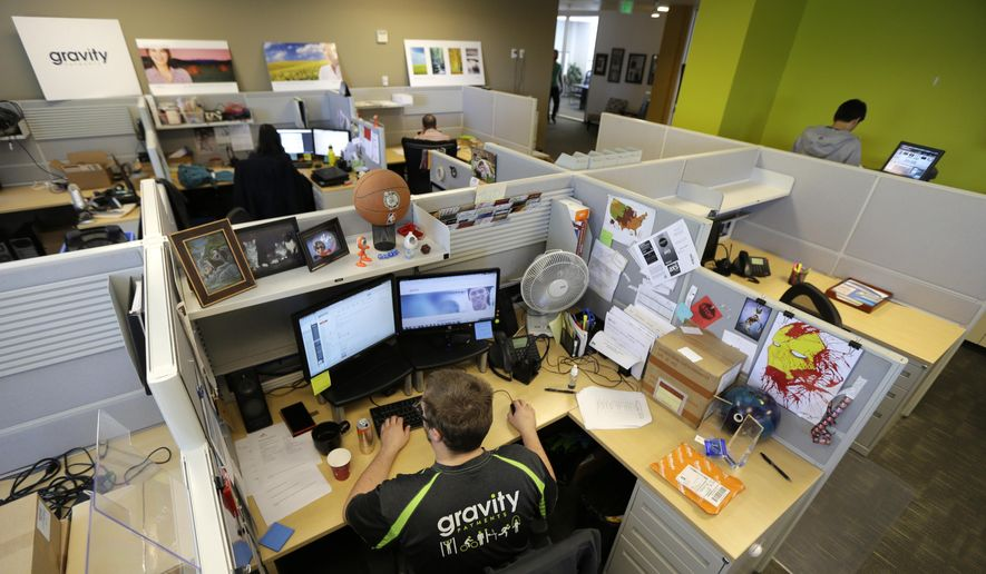 Austin Roos, a support team supervisor, works at lower left, Wednesday, April 15, 2015, at Gravity Payments, a credit card payment processor based in Seattle. Gravity CEO Dan Price told his employees this week that he was cutting his roughly $1 million salary and using company profits so they would each earn a base salary of $70,000, to be phased in over three years. (AP Photo/Ted S. Warren) ** FILE **