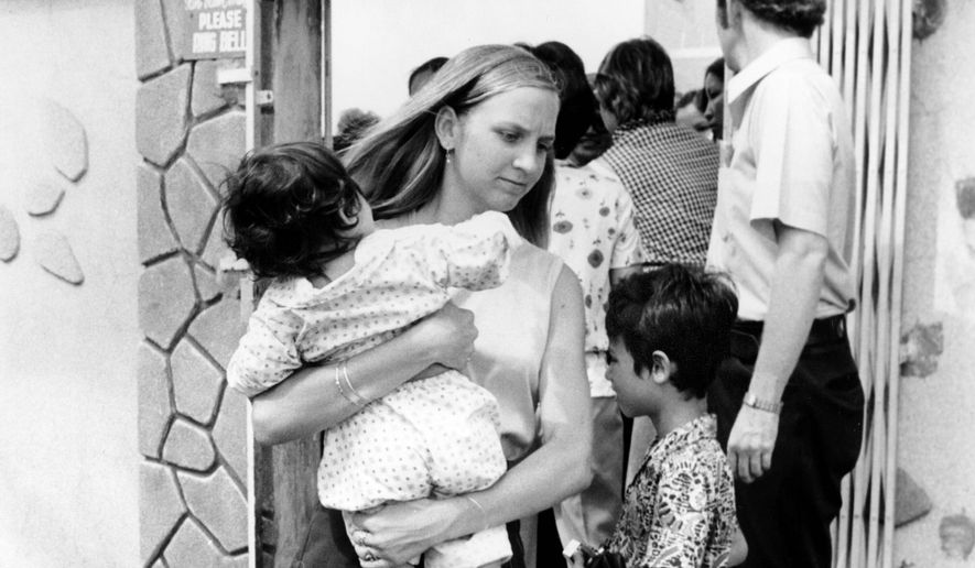 An American volunteer carries a South Vietnamese infant from a Saigon orphanage to the airport en route to the United States for adoption. More than 3,000 young Vietnamese children who were rescued during Operation Babylift in April 1975. (Associated Press)