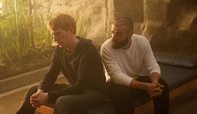 """In this image released by A24 Films, Domhnall Gleeson, left, and Oscar Isaac appear in a scene from """"Ex Machina."""" (AP Photo/A24 Films)"""