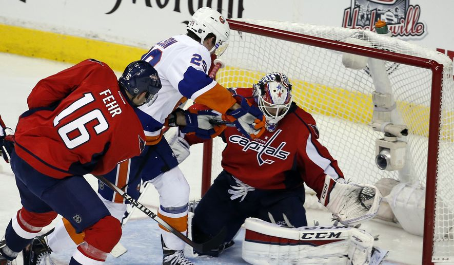 Washington Capitals right wing Eric Fehr (16) defends with goalie Braden Holtby (70) as New York Islanders center Brock Nelson (29) works in front of the net during the third period in the opening game of a first-round NHL hockey playoff series, Wednesday, April 15, 2015, in Washington. The Islanders won 4-1. (AP Photo/Alex Brandon)