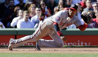 Washington Nationals third baseman Yunel Escobar fields a ground out by Boston Red Sox catcher Sandy Leon during the sixth inning of a baseball game at Fenway Park in Boston, Wednesday, April 15, 2015. (AP Photo/Charles Krupa)