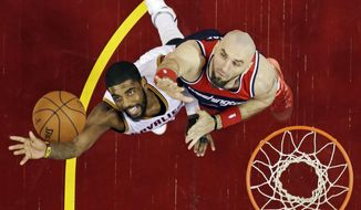 Cleveland Cavaliers' Kyrie Irving, left, shoots on Washington Wizards' Marcin Gortat in the first half of an NBA basketball game Wednesday, April 15, 2015, in Cleveland. (AP Photo/Mark Duncan)
