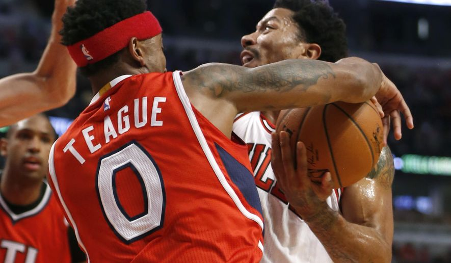 Atlanta Hawks guard Jeff Teague (0) disrupts the drive of Chicago Bulls guard Derrick Rose, during the first half of an NBA basketball game Wednesday, April 15, 2015, in Chicago. (AP Photo/Charles Rex Arbogast)
