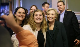 Democratic presidential candidate Hillary Rodham Clinton poses for a photo with Simpson College student MacKenzie Bills, center, after meeting with Iowa Democratic Party lawmakers at the Statehouse, Wednesday, April 15, 2015, in Des Moines, Iowa. (AP Photo/Charlie Neibergall)
