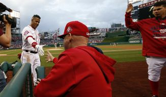 Washington Nationals' Yunel Escobar (5) reaches to shake hands with manager Matt Williams after Escobar's solo home run during the first inning of a baseball game against the Philadelphia Phillies at Nationals Park, Thursday, April 16, 2015, in Washington. (AP Photo/Alex Brandon)