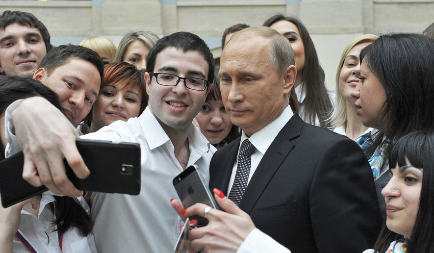 Russian President Vladimir Putin poses for a photo with calling center operators after his live televised call-in show with the nation in Moscow, Russia, Thursday, April 16, 2015. (Mikhail Klimentyev, RIA-Novosti, Presidential Press Service via AP)