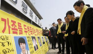 South Korean President Park Geun-hye, second from right, looks at portraits of the victims of the sunken ferry Sewol as she arrives to offer her condolences to the bereaved relatives of the victims at a port in Jindo, South Korea, Thursday, April 16, 2015. (Lee Jeong-ryong/Yonhap via AP)