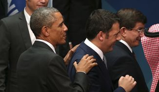 In this Nov. 15, 2014, file photo, U.S. President Baravk Obama left, puts his hands on the shoulders of Prime Minister of Italy Matteo Renzi after the family photo session of the G-20 summit in Brisbane, Australia. Obama will host Renzi at the White House on Friday, April 17, 2015, to compare notes on a range of issues, including Ukraine, Libya and Islamic State militants.  (AP Photo/Rob Griffith, File)
