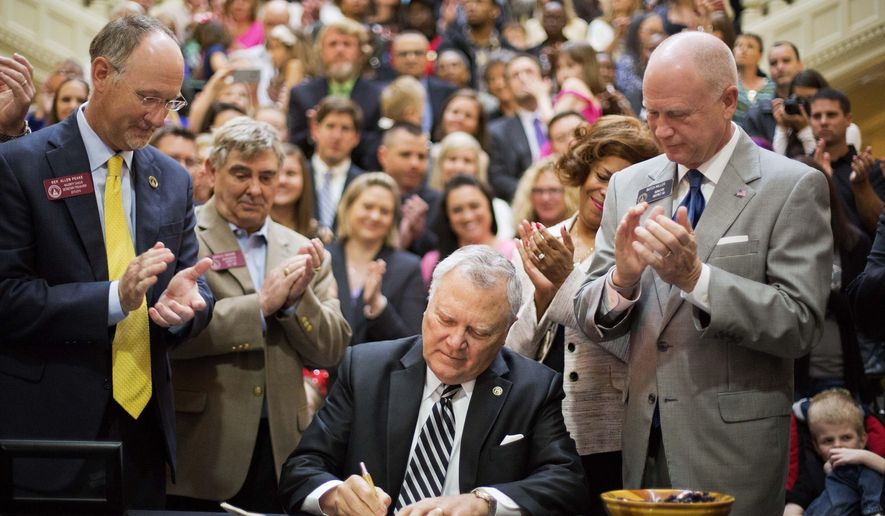 Georgia Gov. Nathan Deal, center, signs a medical marijuana bill into law as the bill's sponsor, Rep. Allen Peake, R-Macon, left, watches on along with Sen. Butch Miller, R-Gainesville, right, during a ceremony at the Statehouse, Thursday, April 16, 2015, in Atlanta. The bill makes Georgia the 38th state to have one and legalizes possession of cannabis oil for treatment of certain medical conditions. (AP Photo/David Goldman)