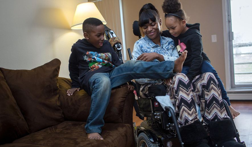 FOR RELEASE MONDAY, APRIL 20, 2015, AT 12:01 A.M. CDT.- Tavaris, left, and Tanaya crawled onto their mother Tanesha Johnson's lap so that the three could watch a movie together Friday, April 10, 2015, in their Brooklyn Center, Minn., apartment. In 2013 Johnson was shot in the neck and paralyzed. After living in a nursing home, she is trying to reunite her family, but struggles to find accessible, affordable housing. (Jennifer Simonson/Minnesota Public Radio via AP)