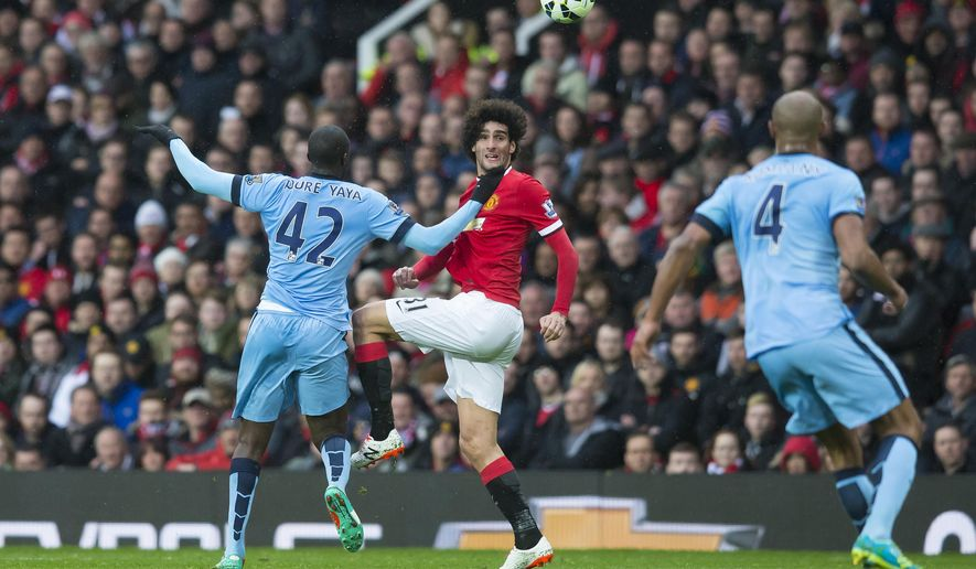 Manchester United's Marouane Fellaini, centre, fights for the ball against Manchester City's Yaya Toure, left, as Vincent Kompany looks on during the English Premier League soccer match between Manchester United and Manchester City at Old Trafford Stadium, Manchester, England, Sunday, April 12, 2015. (AP Photo/Jon Super)