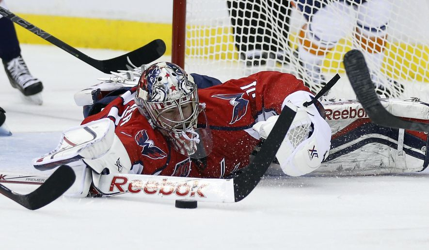 against the Washington Capitals goalie Philipp Grubauer, from Germany, lunges to knock the puck away during the second period of Game 2 against the New York Islanders in a first-round NHL hockey playoff series, Friday, April 17, 2015, in Washington. (AP Photo/Alex Brandon)