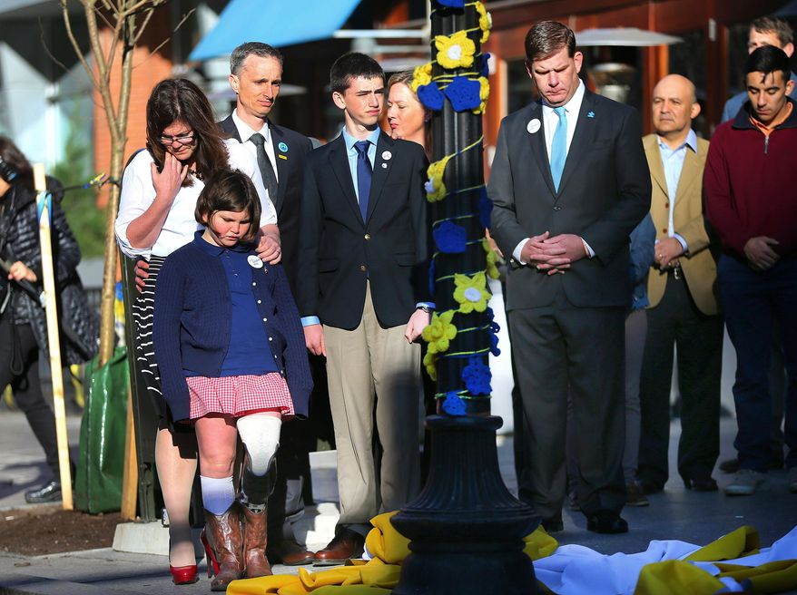 Boston Mayor Marty Walsh, right, looks down after Boston Marathon survivor Jane Richard, left, and her brother Henry removed a drape covering a memorial honoring victims and survivors at one of two blast sites near the finish line of the Boston Marathon in Boston, Wednesday, April 15, 2015.  Parents, Bill and Denise Richards, back,  stood by during the unveiling. Boston marked the second anniversary of the 2013 marathon bombings with a subdued remembrance that includes a moment of silence, the pealing of church bells and a call for kindness. The children lost their brother Martin Richard while standing with him during one of the explosions. (John Tlumacki/The Boston Globe via AP)