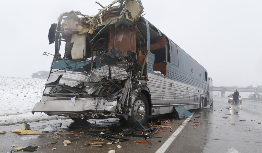 Investigators look over a tour bus involved in an accident with a tractor trailer Friday, April 17, 2015, in Aurora, Colo. At least 11 people were injured, two of them critically, in the four-vehicle wreck that shut down Interstate 70 for several hours during a spring storm packing heavy rains and fog. (AP Photo/David Zalubowski)