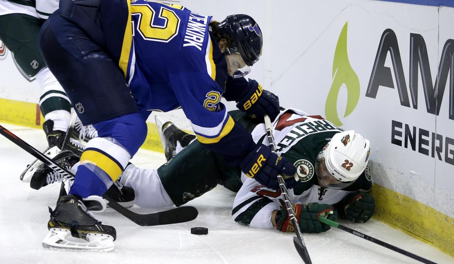 St. Louis Blues' Kevin Shattenkirk, left, and Minnesota Wild's Nino Niederreiter, of Switzerland, get tangled up along the boards during the third period in Game 1 of an NHL hockey first-round playoff series, Thursday, April 16, 2015, in St. Louis. The Wild won 4-2. (AP Photo/Jeff Roberson)