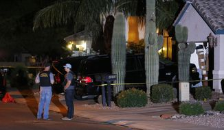 Phoenix Police Department officers stand out in front of a home where authorities say five people were killed inside after a shooting Thursday, April 16, 2015, in Phoenix. The names and ages of the three men and two women weren't immediately released, but police said they all were adults. (AP Photo/Ross D. Franklin)