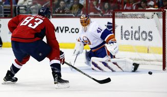 Washington Capitals center Jay Beagle (83) has his shot blocked by New York Islanders goalie Jaroslav Halak (41), from Slovakia, during the first period of Game 2 in the first round of the NHL hockey Stanley Cup playoffs, Friday, April 17, 2015, in Washington. (AP Photo/Alex Brandon)