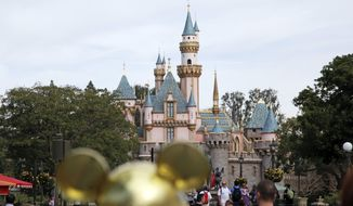 FILE - In this Jan. 22, 2015 file photo, visitors walk toward the Sleeping Beauty's Castle in the background at Disneyland Resprt in Anaheim, Calif. California health officials have declared an end to the large measles outbreak that originated at Disneyland in December. (AP Photo/Jae C. Hong, File)